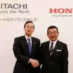 Honda Chief Executive Officer Takahiro Hachigo and his Hitachi Automotive counterpart Hideaki Seki shake hands at a photo session after their news conference in Tokyo